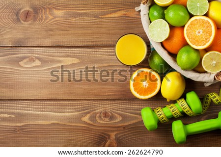 Citrus fruits in basket and dumbells. Oranges, limes and lemons. Over wood table background with copy space - stock photo