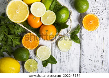 Citrus fruits in basket. Oranges, limes and lemons. Over white wood table background with copy space