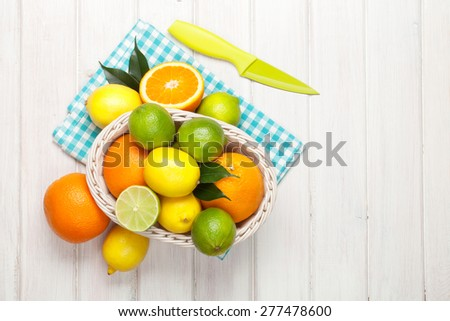 Citrus fruits in basket. Oranges, limes and lemons. Over wooden table background with copy space - stock photo