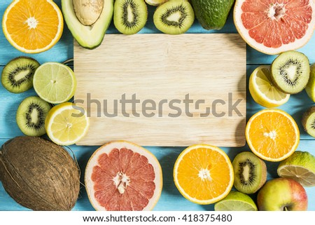 citrus fruits in the center of a wooden board on a blue table top view - stock photo