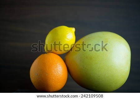 Citrus fruits include pomelo, lime, and orange are mix in a closeup view. - stock photo