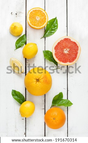 Citrus fruits (lemon, grapefruit and orange) with fresh wet leaves on white planked wooden table - still life from above - stock photo