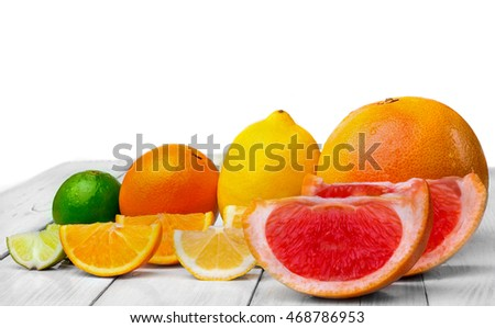 Citrus fruits (lemon, grapefruit. lime and orange) arranged in a row whole and slices. On wooden table(background). White background.