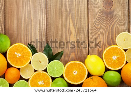 Citrus fruits. Oranges, limes and lemons. Over wood table background with copy space - stock photo