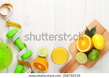 Citrus fruits, tape measure and dumbells. Oranges, limes and lemons. Healthy food. Over wood table background with copy space - stock photo