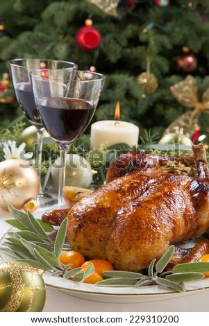 Citrus glazed roasted duck stuffed with rice, garnished with apples, kumquats, and sage. Christmas decorated setting.  - stock photo