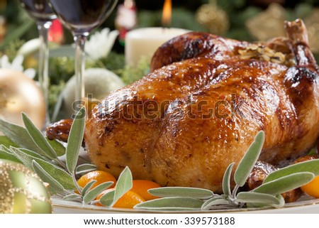 Citrus glazed roasted duck stuffed with rice, garnished with apples, kumquats, and sage. Christmas decorated setting.