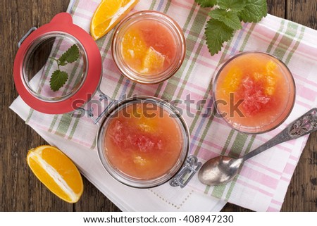Citrus jelly in a glass jar. Homemade grapefruit orange gelatin dessert. Healthy low fat and low calorie meal. Top view. - stock photo