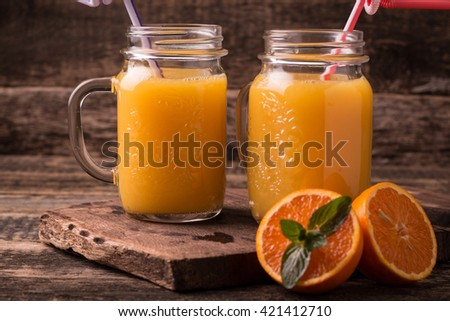 Citrus juice and fruits on wooden background.  - stock photo