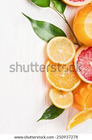 Citrus  juice and sliced  fruits: orange, lemon and grapefruit on white wooden background - stock photo