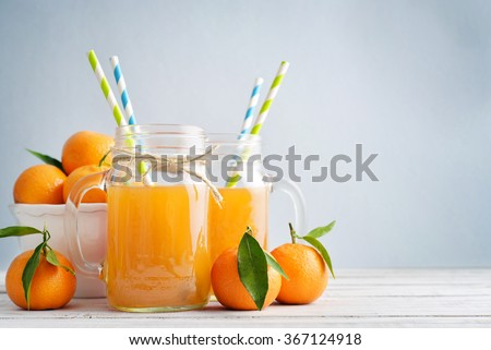 Citrus juice in jar with handle and fresh mandarin orange on blue background - stock photo
