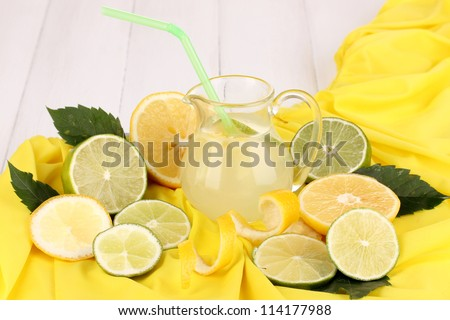 Citrus lemonade in glass pitcher of citrus around on yellow fabric on white wooden table close-up