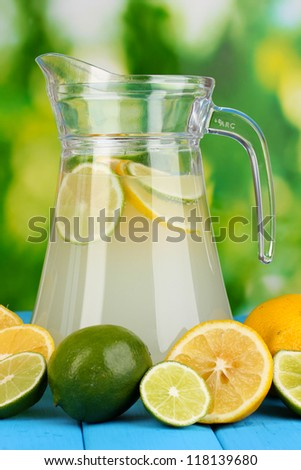 Citrus lemonade in pitcher of citrus around on natural wooden table on blue background - stock photo
