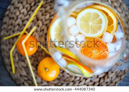 citrus lemonade. Lemonade with oranges, lemons and tangerines. Lemonade with ice. Lemonade in a glass jug. Straws to drink lemonade.