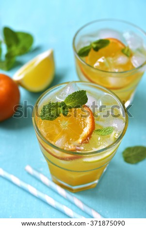 Citrus lemonade with mint on a turquoise background. - stock photo