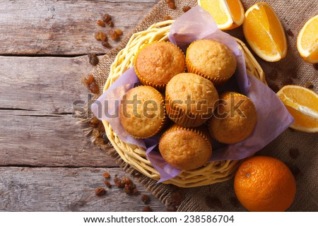 Citrus muffins in a basket and fresh oranges on an old table close-up. horizontal view from above  - stock photo