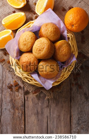 Citrus muffins in a basket and fresh oranges on an old table close-up. Vertical view from above  - stock photo