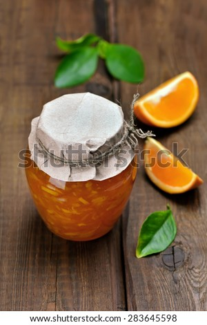 Citrus orange jam in glass jar on wooden table - stock photo