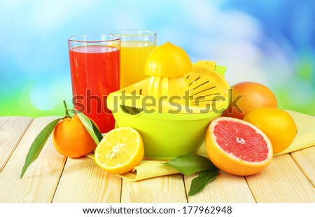 Citrus press and fruits on table on blue background