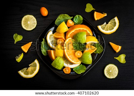 Citrus salad on black background. Slices citrus fruits. Top view, flat lay - stock photo