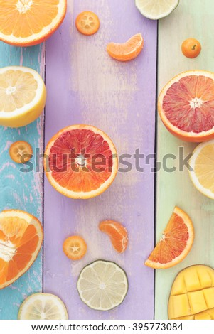 Citrus Salad with Mango, ingredients. Colorful sliced fruits background, ingredients for mango citrus salad . Top view, vintage toned image, blank space  - stock photo