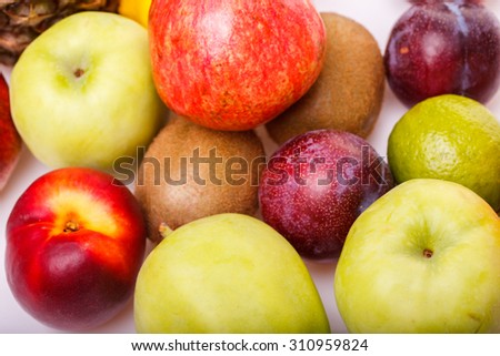Citrus tropical colorful fruits of orange juicy grapefruit yellow lemon ripe nectarine purple plum red pomegranate kiwi lime and green apple on studio white background closeup, horizontal picture