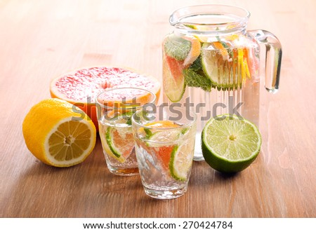Citrus water with mint in jar and glasses - stock photo