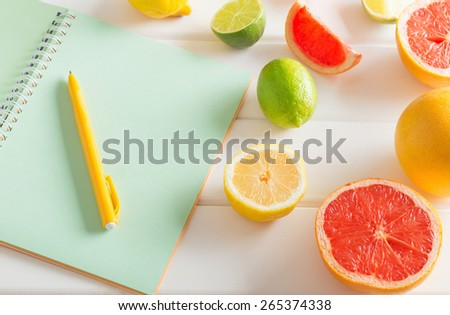 citrus with notebook on white wooden table - stock photo