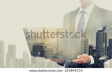 city and businessman using laptop computer. conceptual business image - stock photo