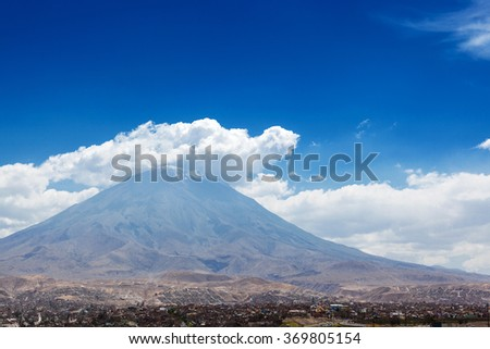 city and the volcano on a background of sky - stock photo