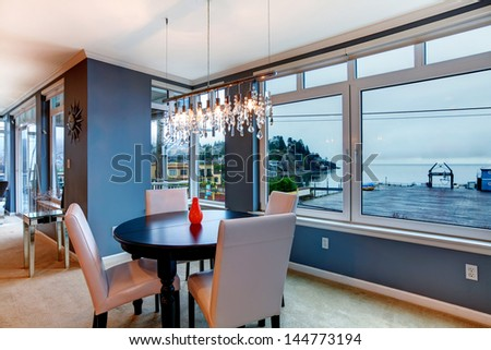City apartment dining room with round small table and blue walls. - stock photo