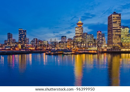 City at night, panoramic scene of downtown reflected in water, Vancouver, Canada. - stock photo