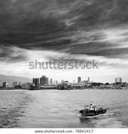 City bay with single boat and skyscrapers in Penang, Malaysia, Asia. - stock photo