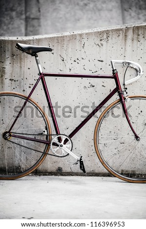 City bicycle fixed gear and concrete wall, commuting to work in city, vintage retro style bike over grunge city urban environment, ecological transportation concept
