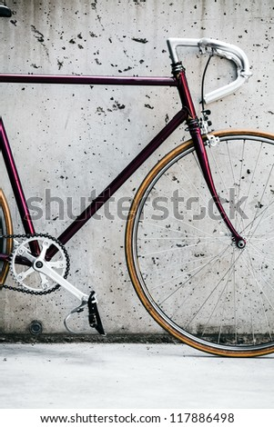 City bicycle fixed gear and concrete wall, vintage style closeup on bike frame, vintage old retro bike, cycling or commuting in city urban environment, ecological transportation concept - stock photo