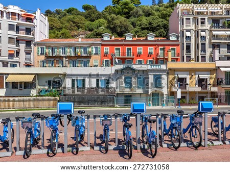 City bicycles at sharing station and colorful houses on background in Nice, France. - stock photo