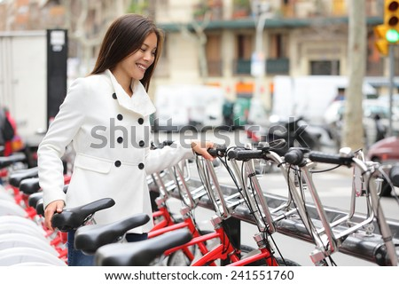 City bike - woman using public city bicycles sharing system. Biking female professional parking city bikes after cycling on city bicycle. Barcelona, Spain, Europe. - stock photo