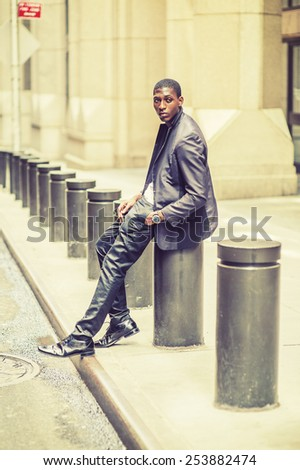 City Boy. Wearing fashionable jacket, pants, leather shoes, wristwatch, a young black teenage boy is sitting on street, looking around, waiting for you. Street Fashion. Retro filtered look. - stock photo