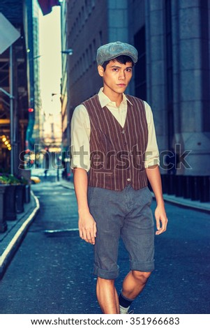 City Boy. Wearing newsboy cap, light yellow shirt, patterned vest, gray pants, Asian American college student walking on narrow street with high buildings in New York. Instagram filtered effect.