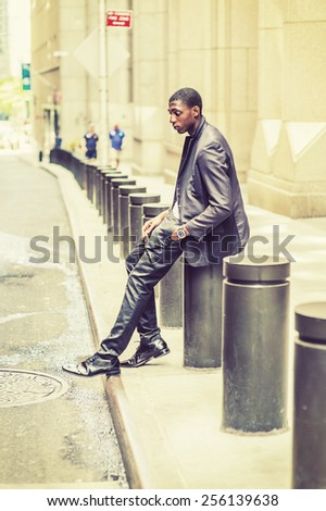 City Boy. Young black college student sitting on street, hunchbacked, sad, tired, looking down, lost in thought. Concept of teenagers questioning life, career, self esteem. Retro filtered look. - stock photo