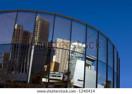 City buildings reflected in the mirrored glass of a city building.