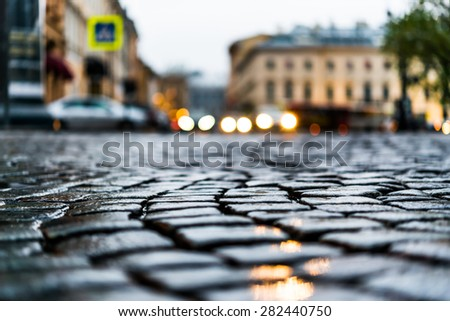 City central square paved with stone after a rain, headlights from cars in the distance. View from the pavement level - stock photo