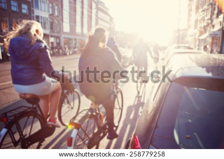 City commuters. High key blurred image of people riding a bike in the street. Unrecognizable faces. - stock photo