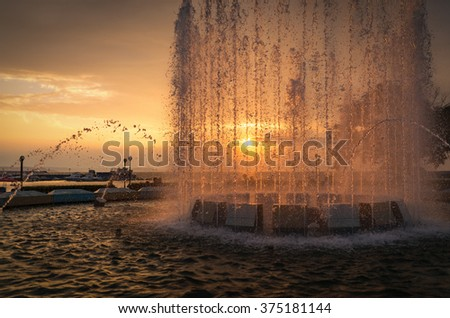 City fountain at sunset. Selective focus with shallow depth of field. - stock photo