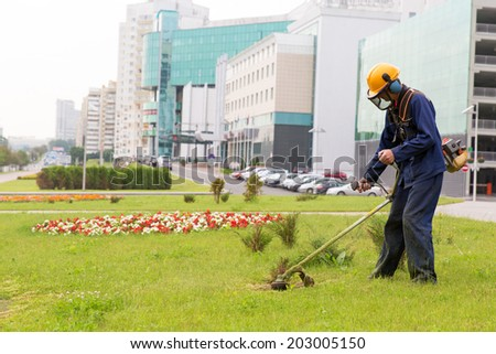 City gardener mowing lawn with gas trimmer - stock photo