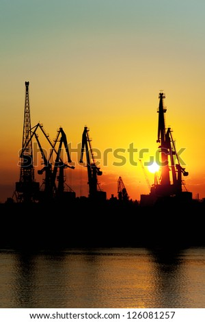 City harbor with loading cranes, evening at sunset.