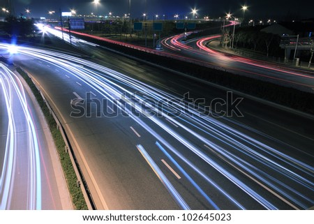 City-highway vehicles in the evening rainbow light trails