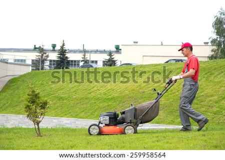 City landscaper cutting grass with lawn mower - stock photo