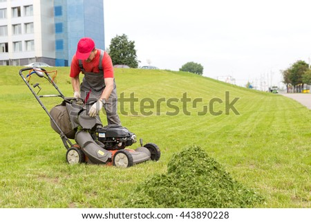 City landscaper worker man stop mower machine and unloading grass from lawn cutter bag - stock photo