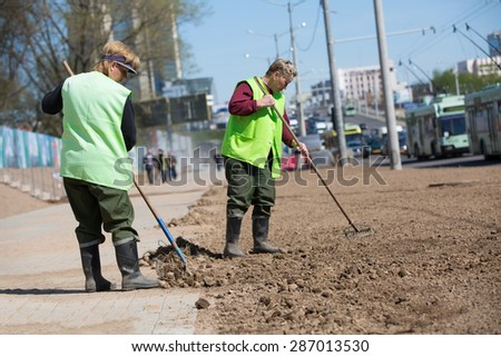 City landscapers female workers preparing soil along street for grass planting with rake tools - stock photo
